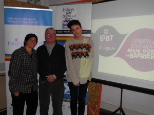 Project manager with two others in front of Rainbow Jews and LGBT history month banners