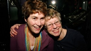 Two women smiling, one with her arm around the other